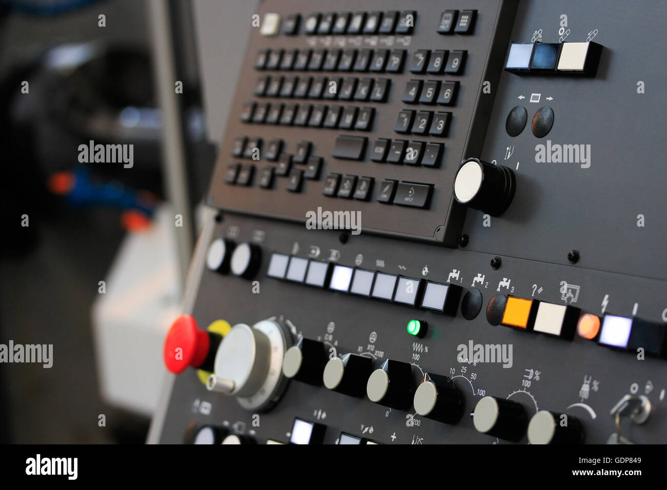Modern CNC machining center with control panel on foreground. Close up view. Selective focus. - Stock Image