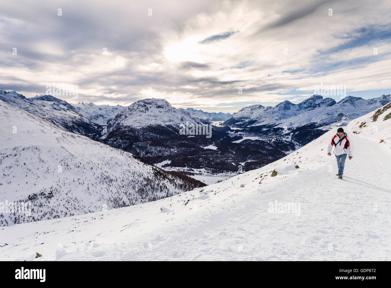 Man walking on snow covered mountain, rear view, Engadine, Switzerland - Stock Image