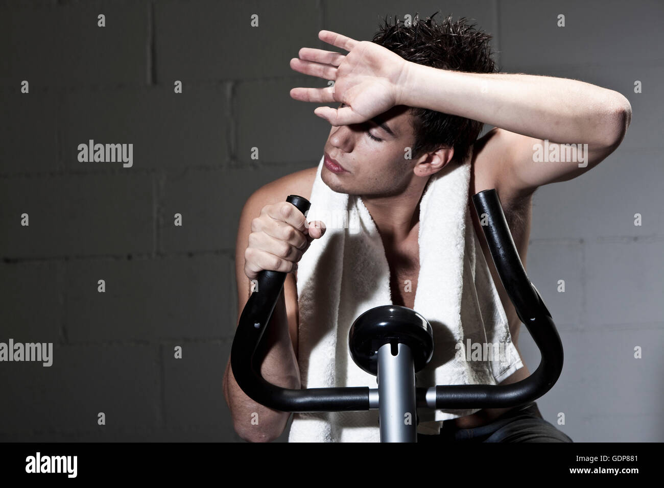 Man using exercise machine moping forehead - Stock Image