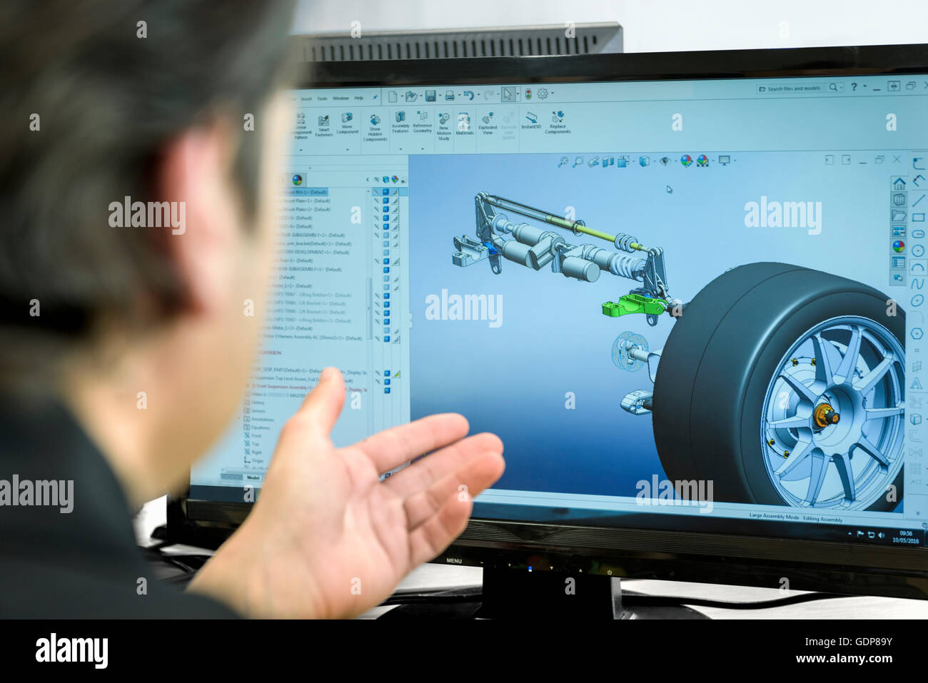 Engineer works with CAD design imagery in racing car factory, close up - Stock Image