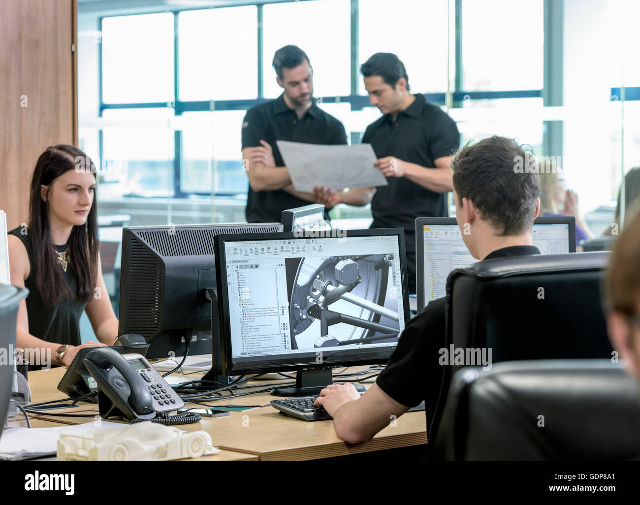 Engineers work with CAD design imagery in racing car factory - Stock Image