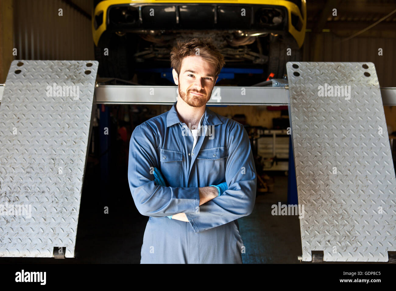 Portrait of male mechanic behind car lift in garage Stock Photo