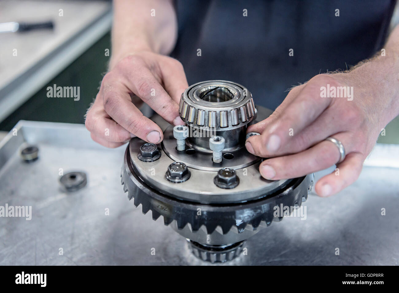 Engineer assembling part in racing car factory - Stock Image