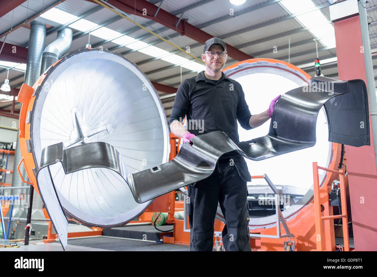 Engineer inspecting carbon fibre body part in front of autoclave in racing car factory Stock Photo