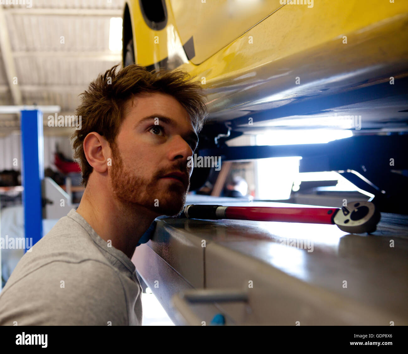 Male mechanic looking underneath sports car - Stock Image