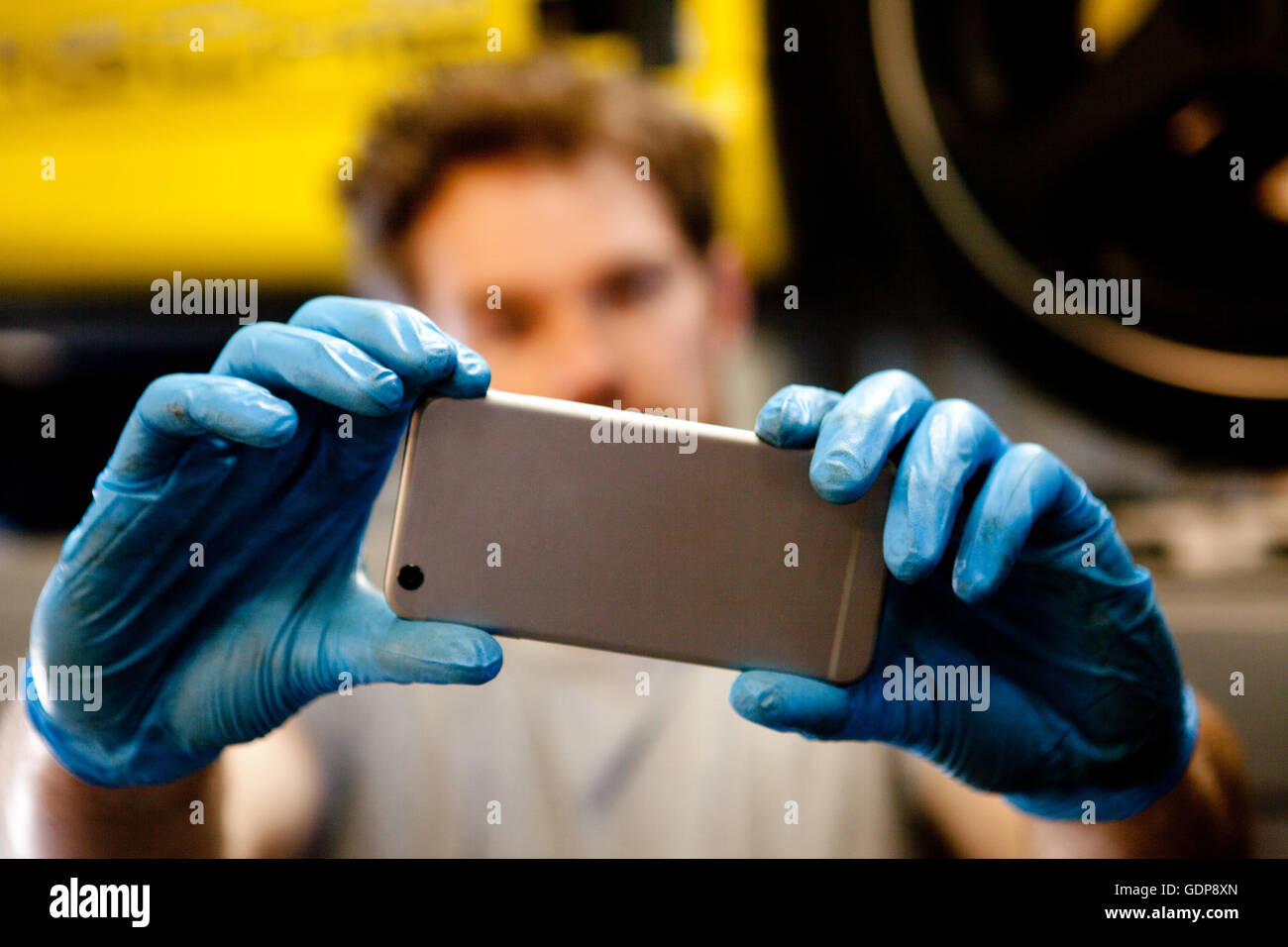Male mechanic in workshop taking photo of car with mobile phone - Stock Image