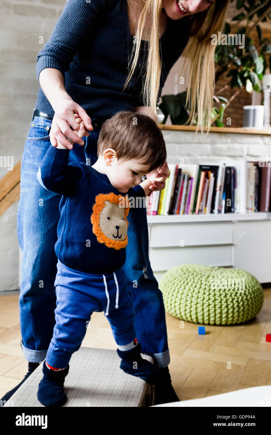 Mid adult woman taking first steps with baby son in living room - Stock Image