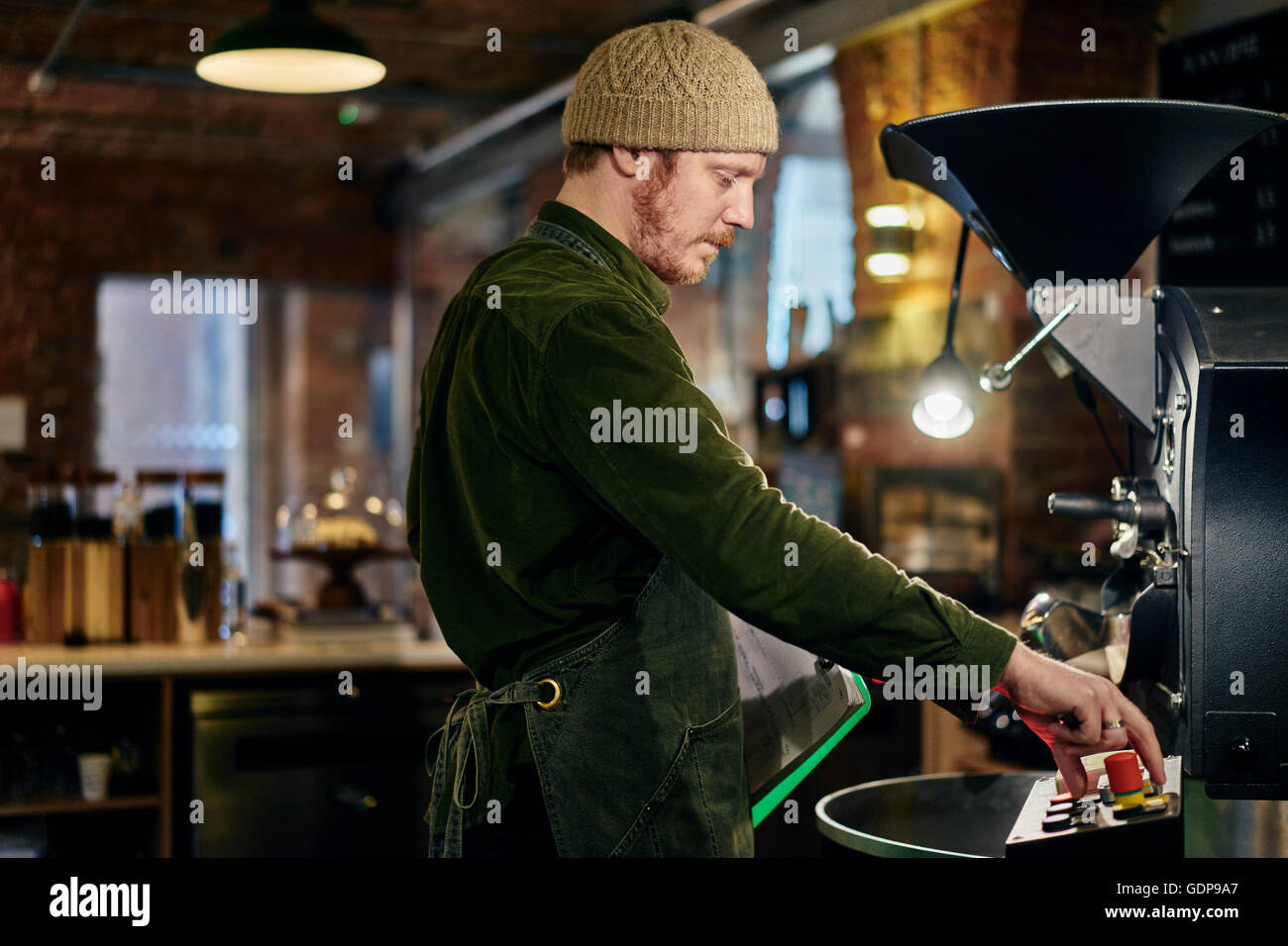 Male coffee shop owner using coffee roaster - Stock Image