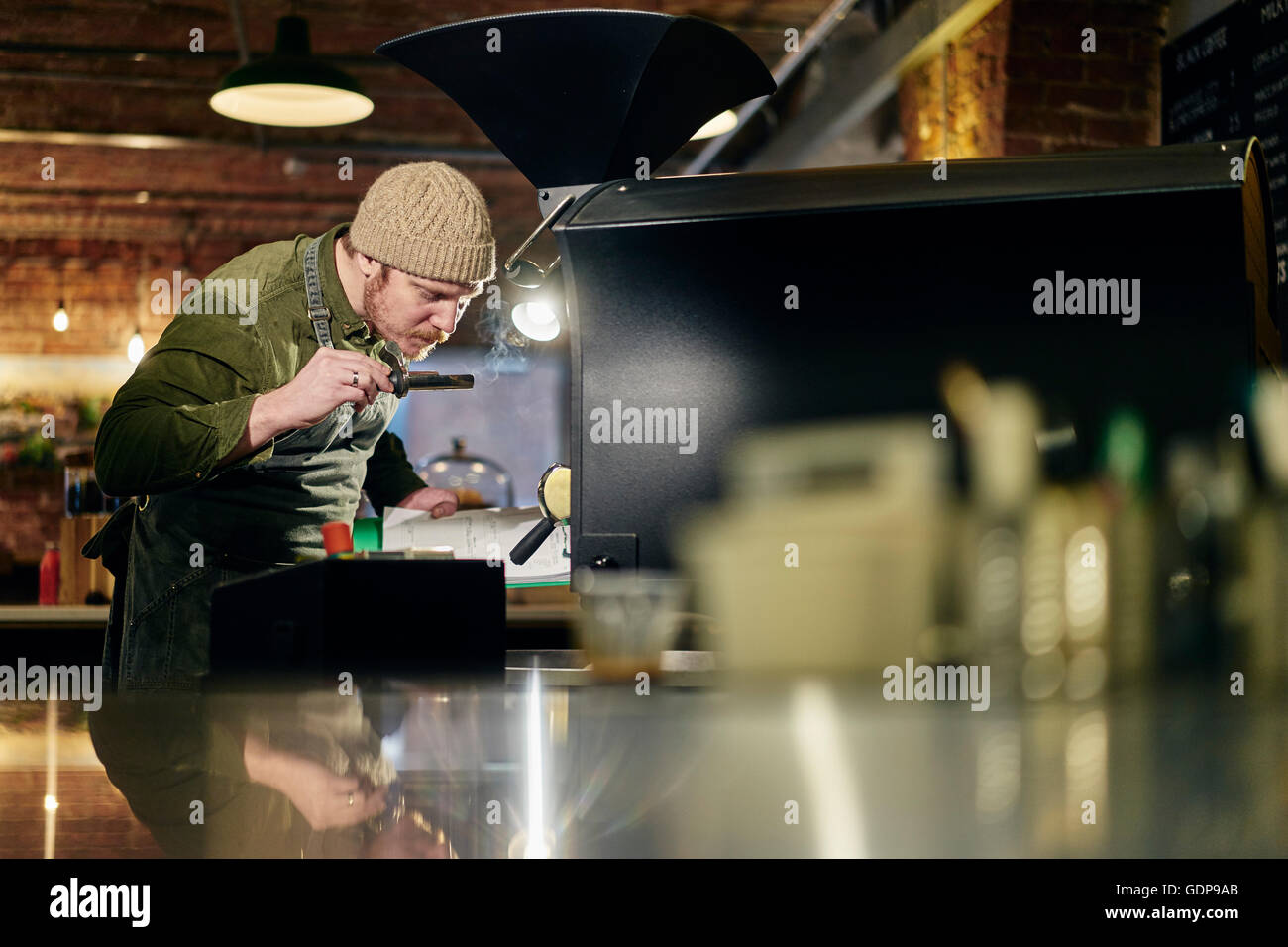 Male coffee shop owner smelling coffee from coffee roaster - Stock Image