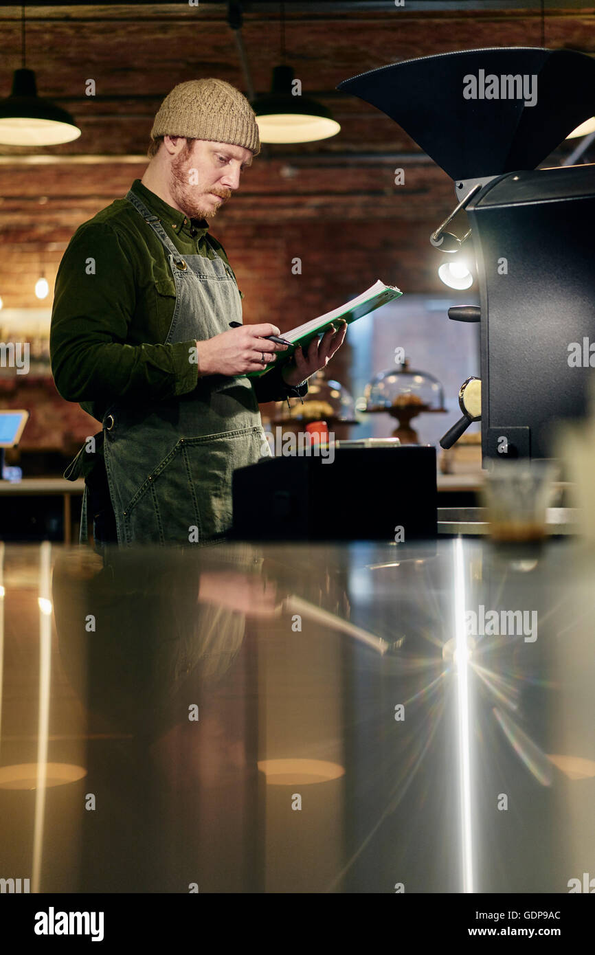 Male coffee shop owner at coffee roaster with clipboard - Stock Image