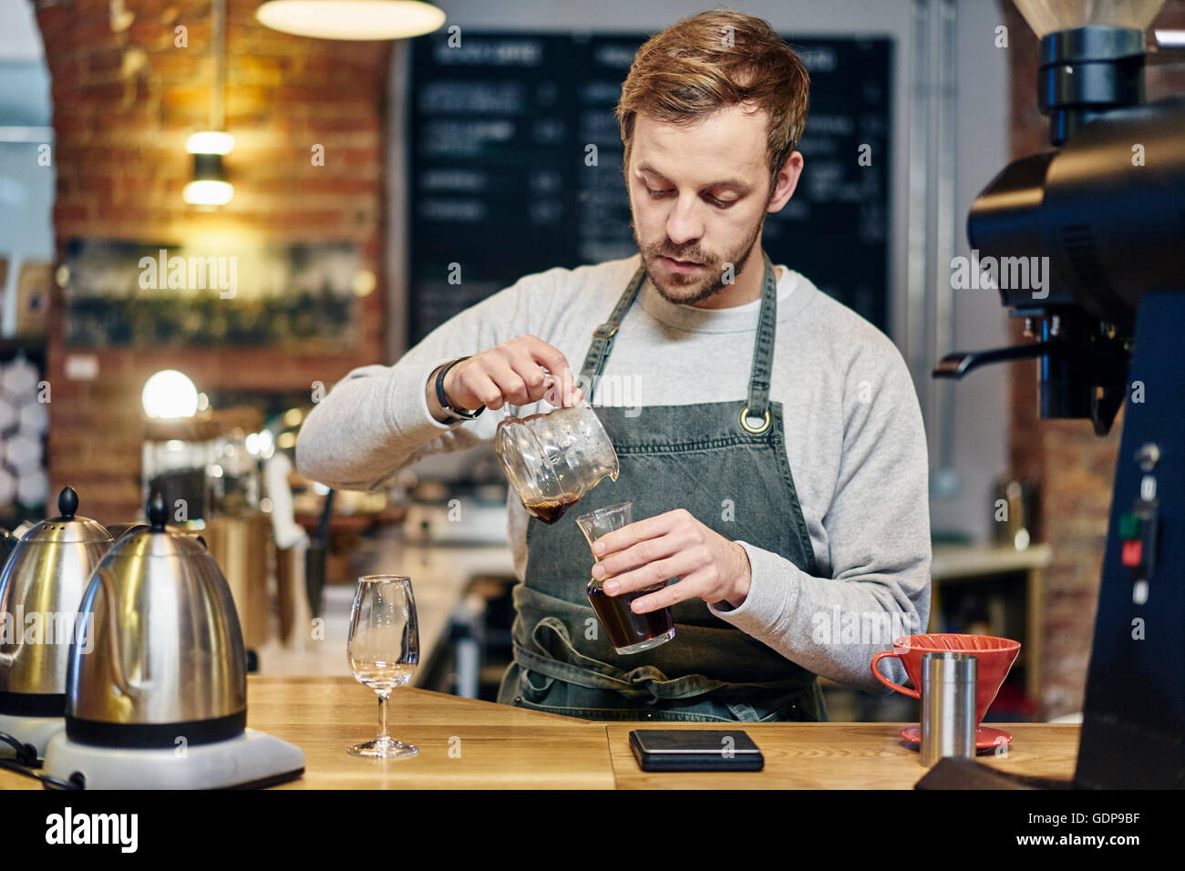 male barista pouring coffee at coffee shop kitchen counter stock photo 111743059 alamy. Black Bedroom Furniture Sets. Home Design Ideas