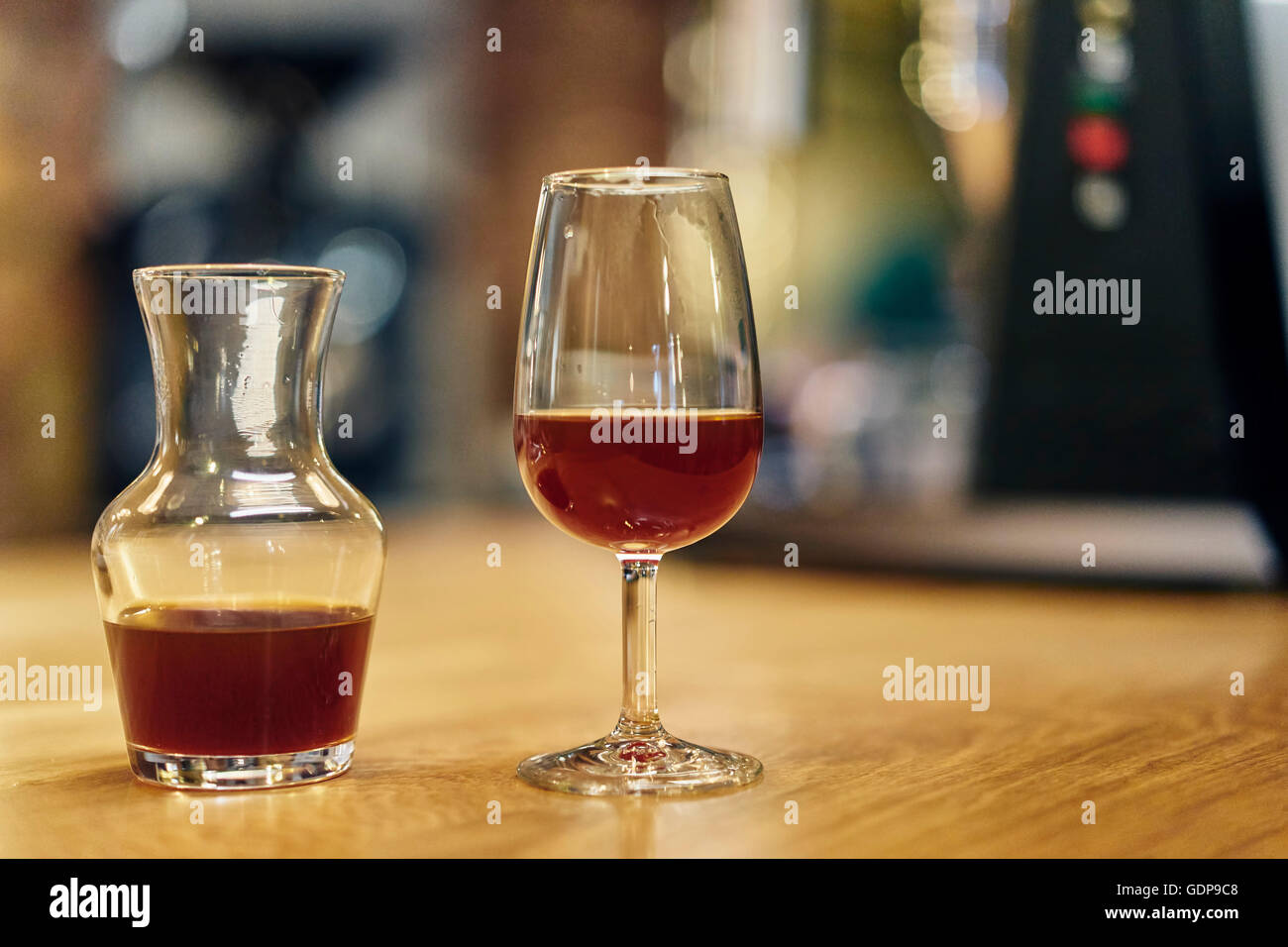 Decanter and wine glass of cold brew coffee on coffee shop counter - Stock Image