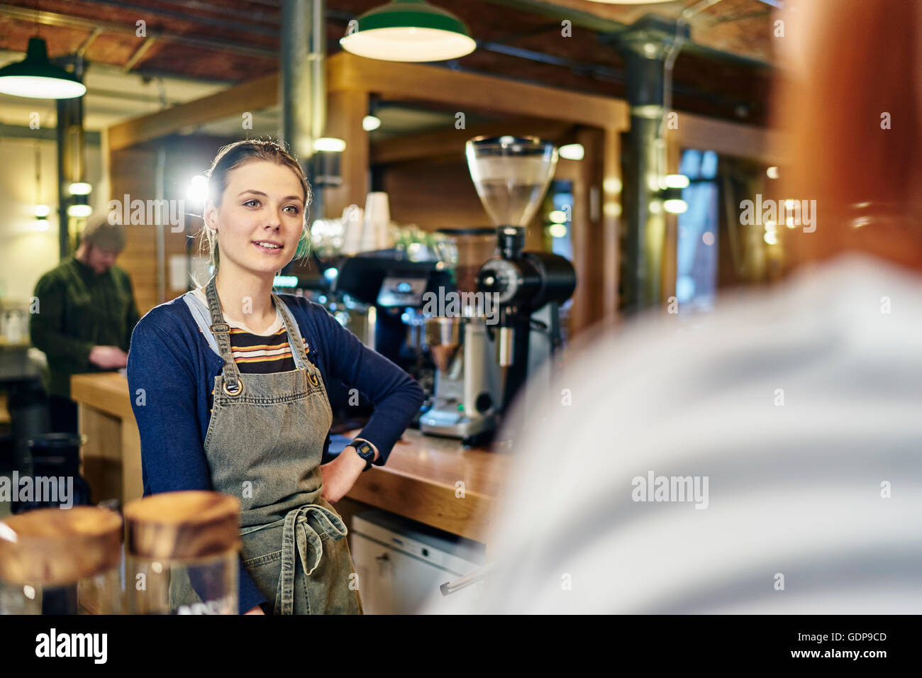 Female barista serving customer in coffee shop - Stock Image