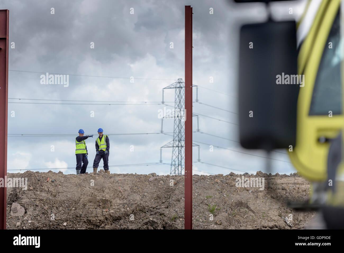 Apprentice builders inspecting building site - Stock Image