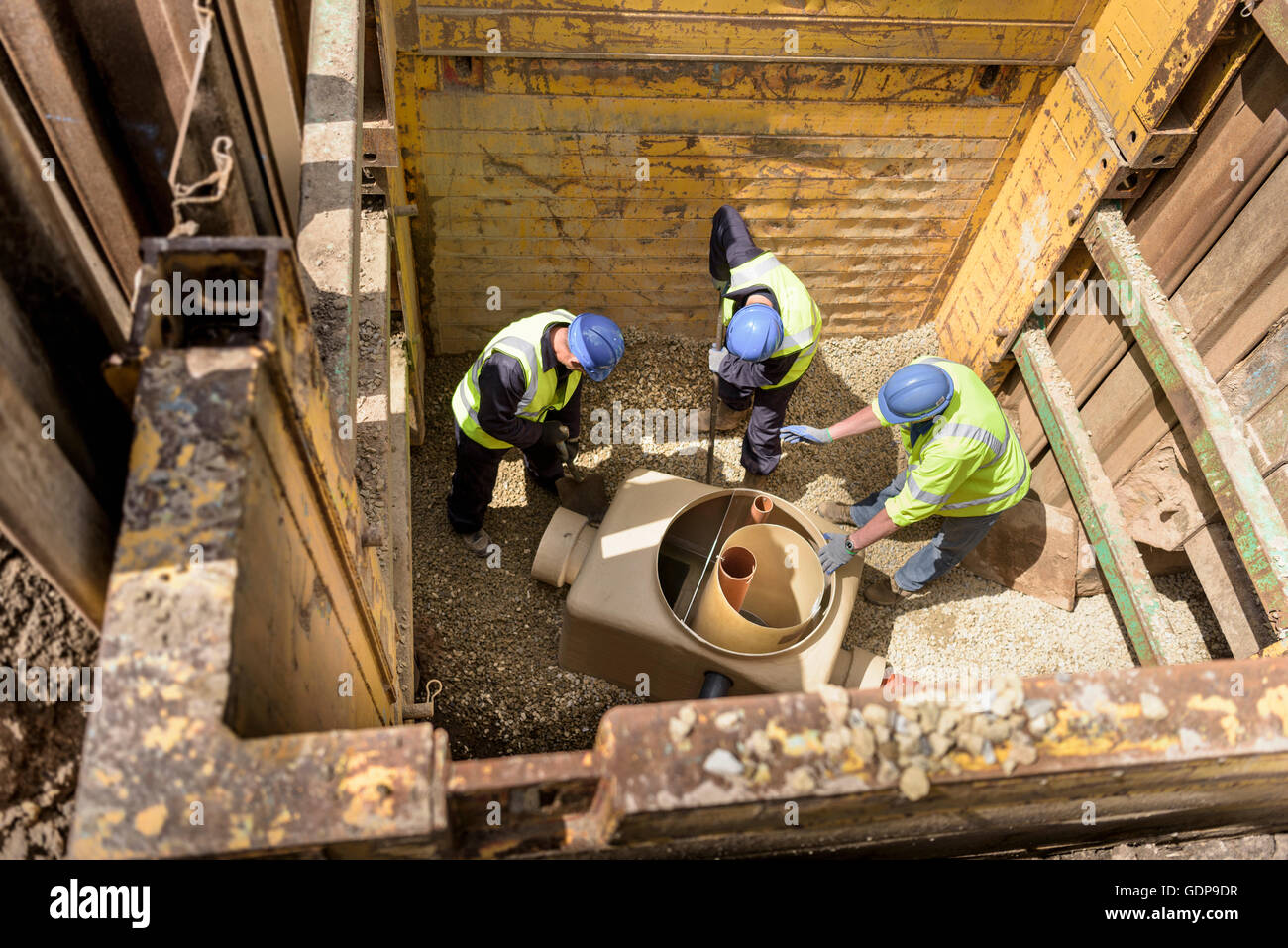 Apprentice builders training with drainage in hole on building site - Stock Image