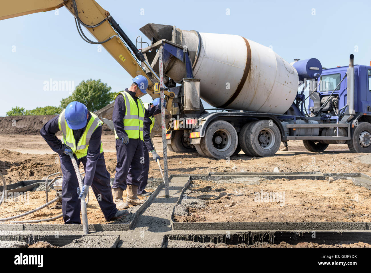 Apprentice builders laying concrete foundations on building site Stock Photo