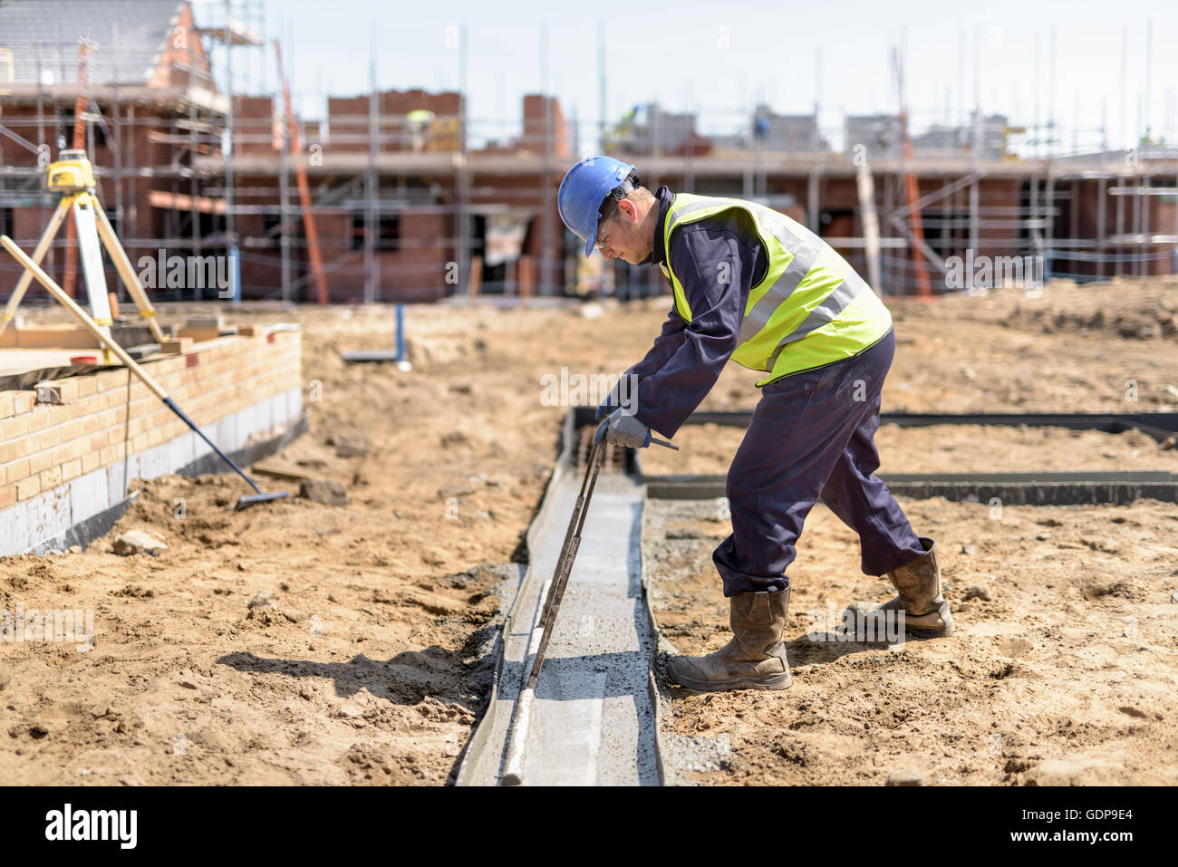 Apprentice builder laying concrete foundations on building site - Stock Image