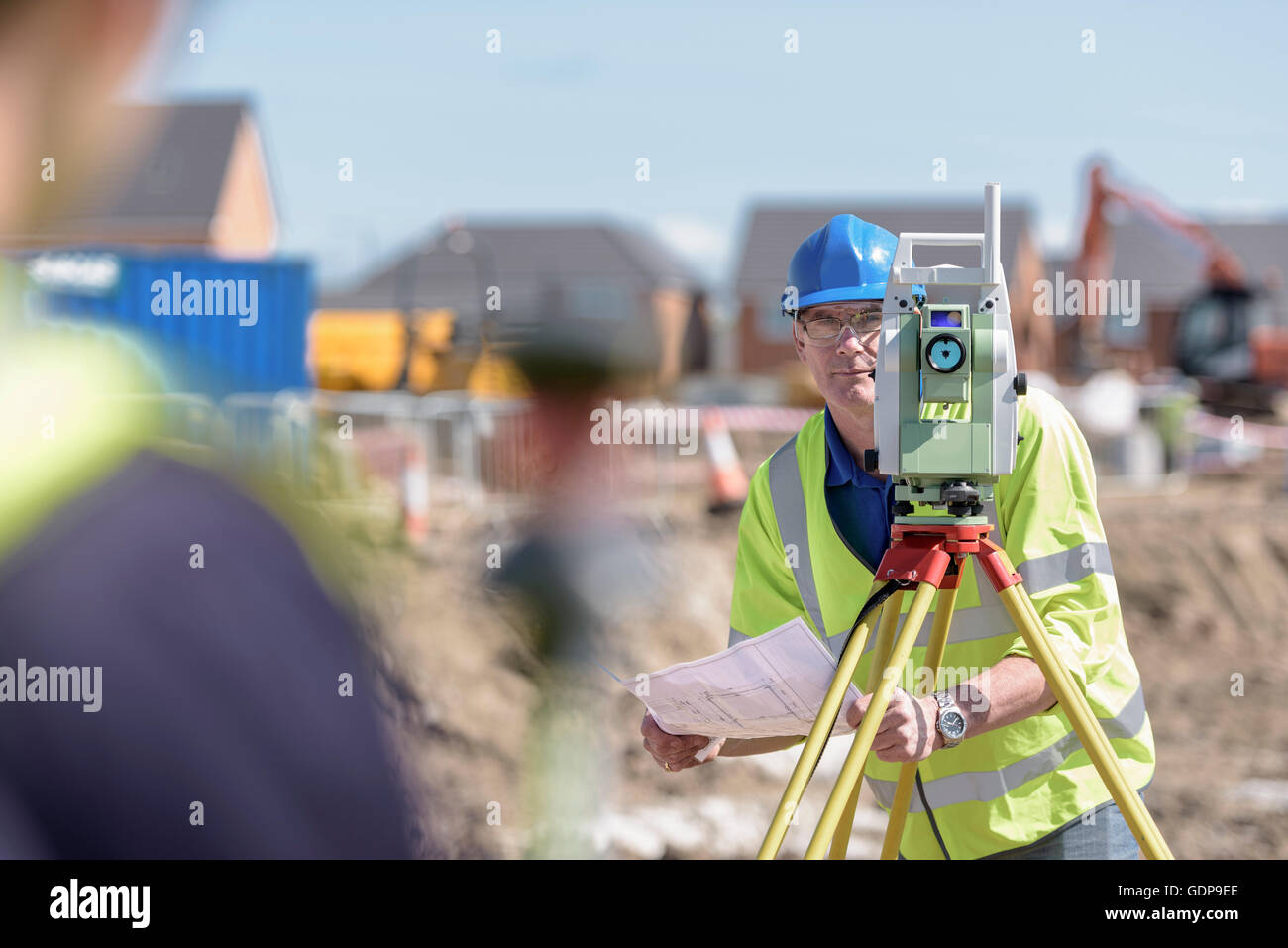 Apprentice builders using theodolite on building site - Stock Image