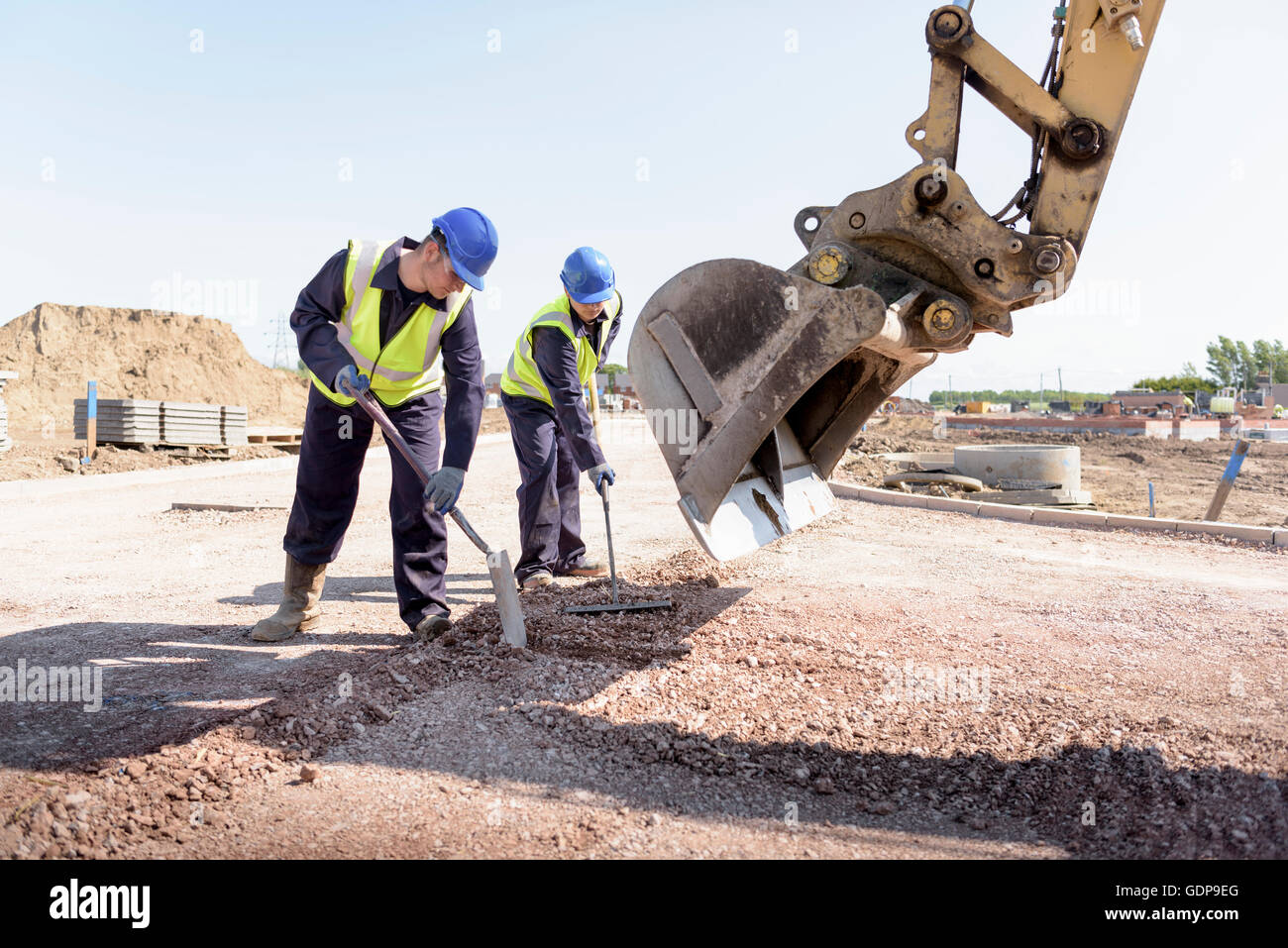Apprentice builders levelling road with digger on building site - Stock Image