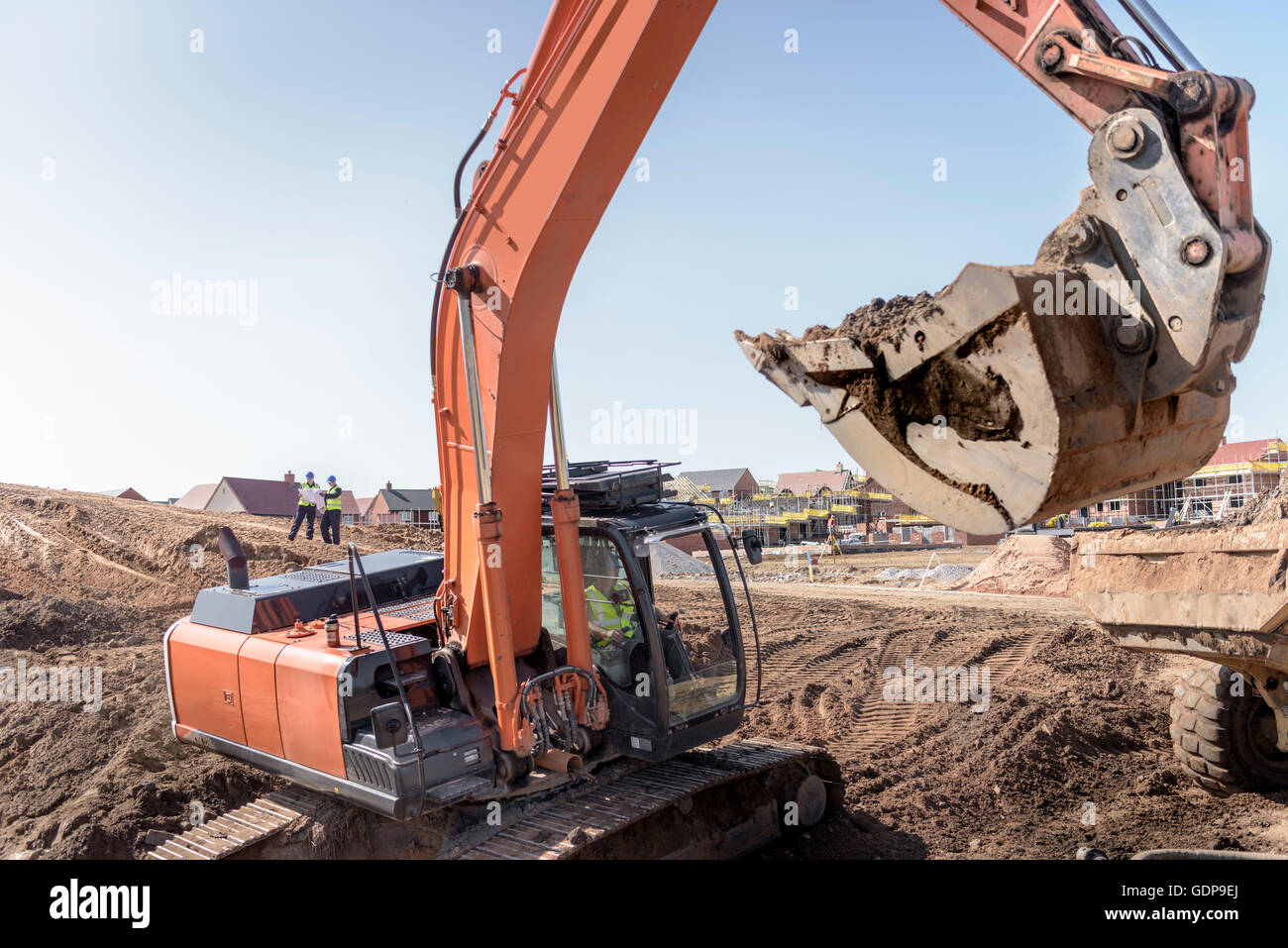 Excavator moving earth on housing building site - Stock Image