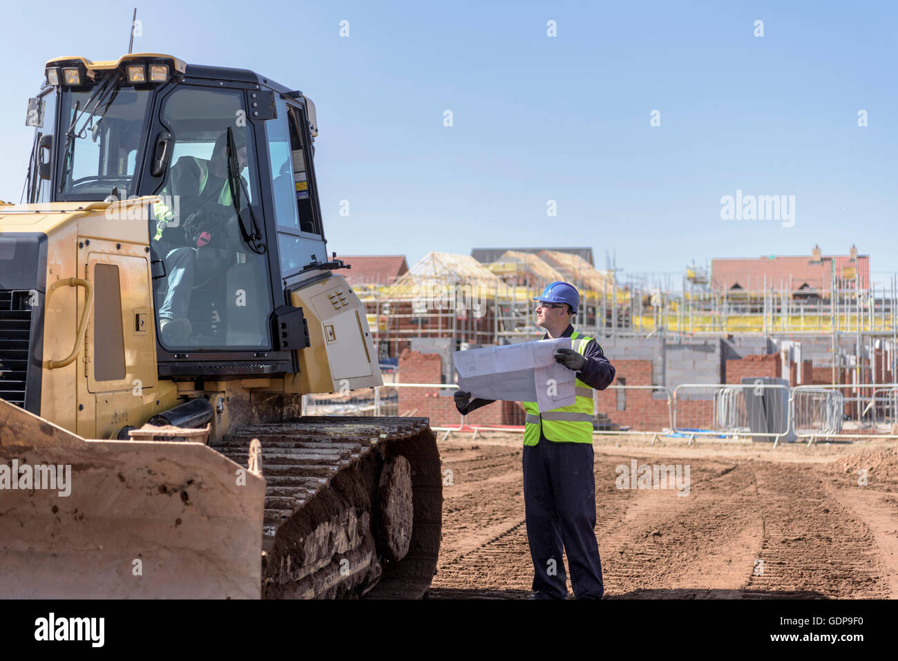 Builder with site plans in discussion with bulldozer driver on housing building site - Stock Image