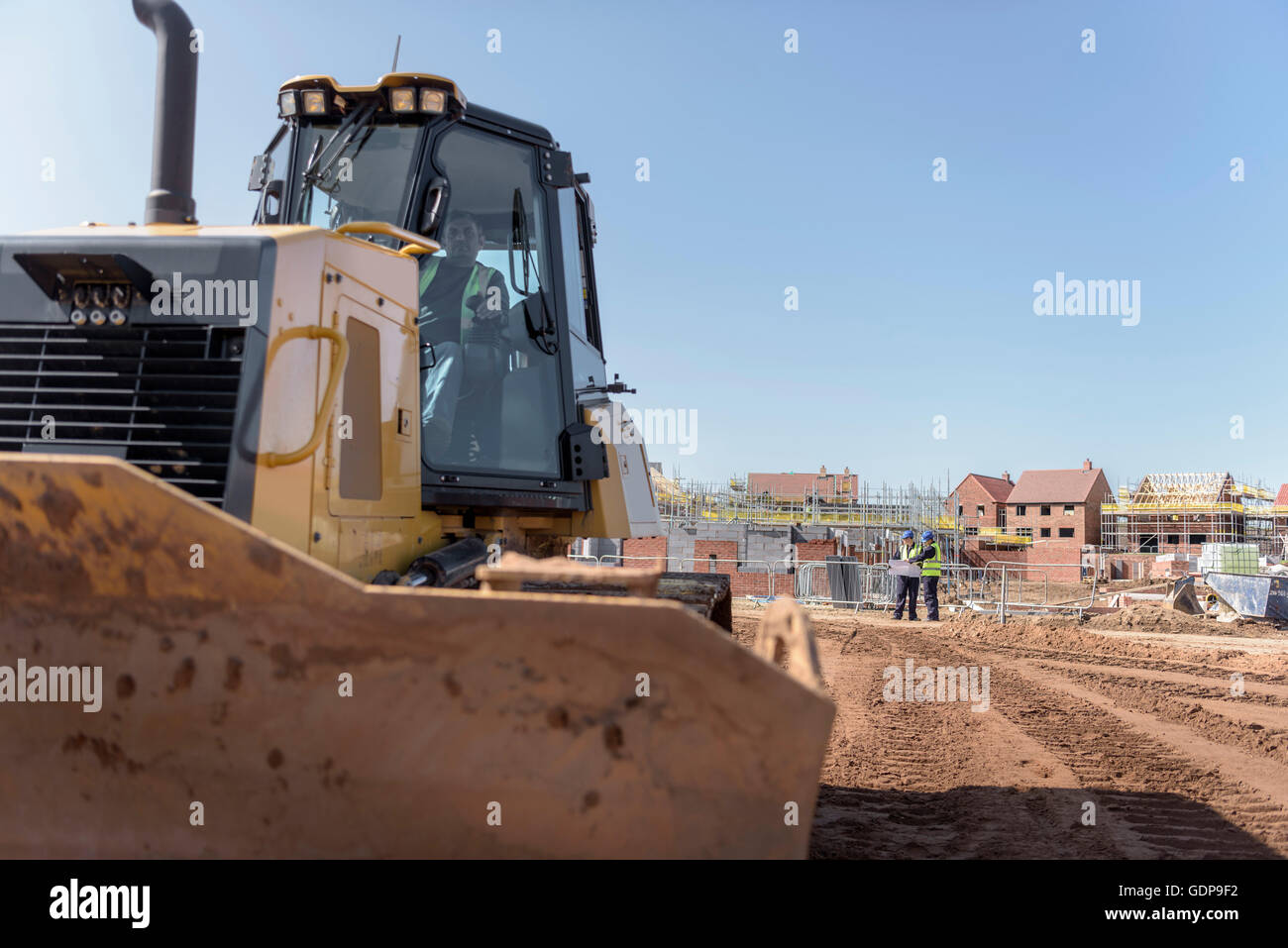 Bulldozer driver on housing building site - Stock Image