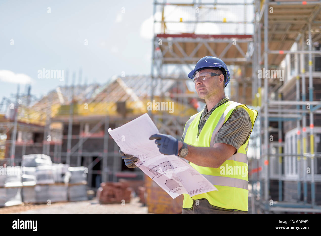 Site manager looking at plans on housing building site - Stock Image