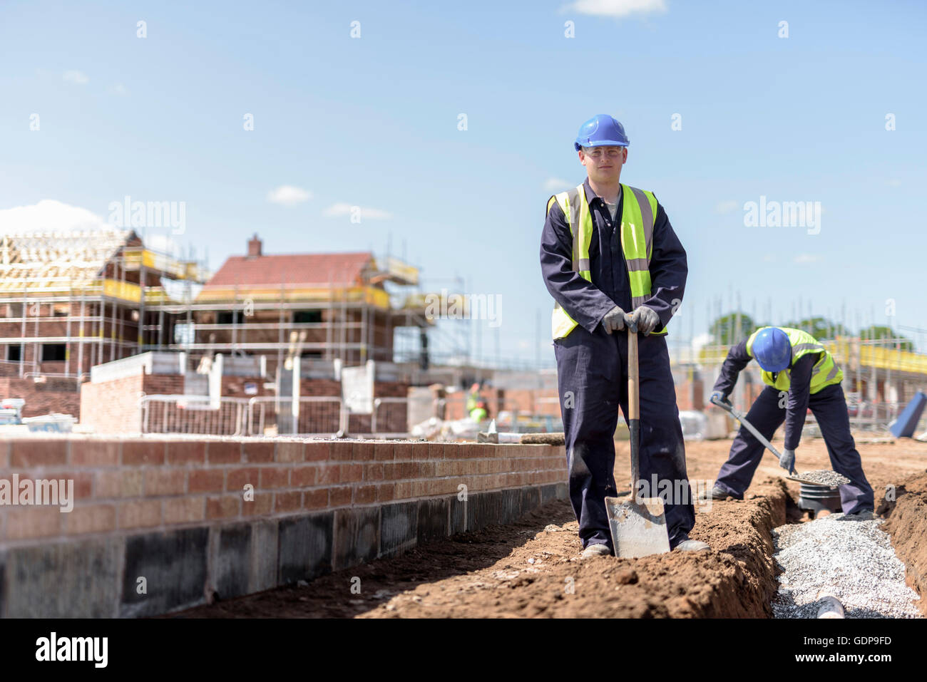 Portrait of apprentice builder laying pipework on housing building site - Stock Image