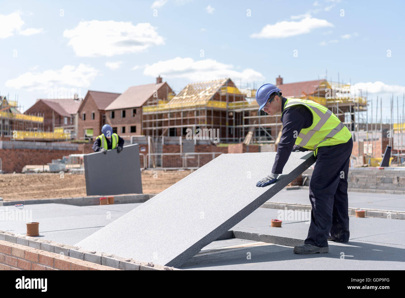 Builders laying insulation on housing building site - Stock Image