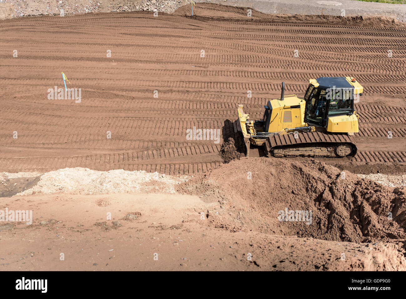 Bulldozer moving earth on housing building site Stock Photo