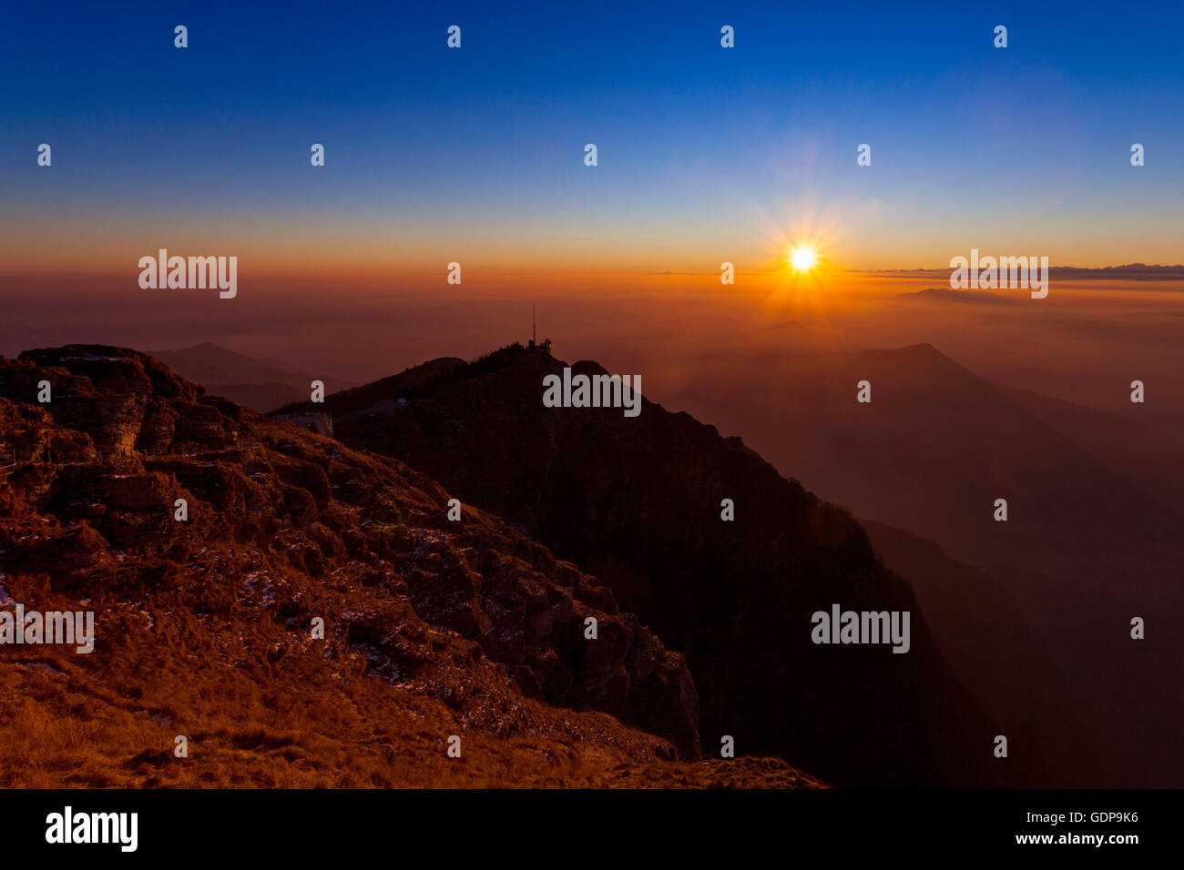 Elevated silhouetted landscape with valley mist at sunset, Monte Generoso,Ticino, Switzerland - Stock Image