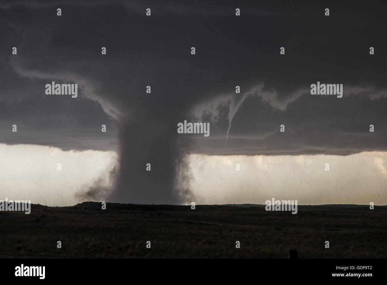 An accessory funnel attempts to touch down while rotating about this very dusty tornado in Colorado - Stock Image