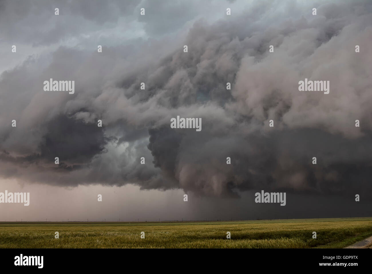 Funnel cloud hovers over a country road while intense updrafts ascend - Stock Image