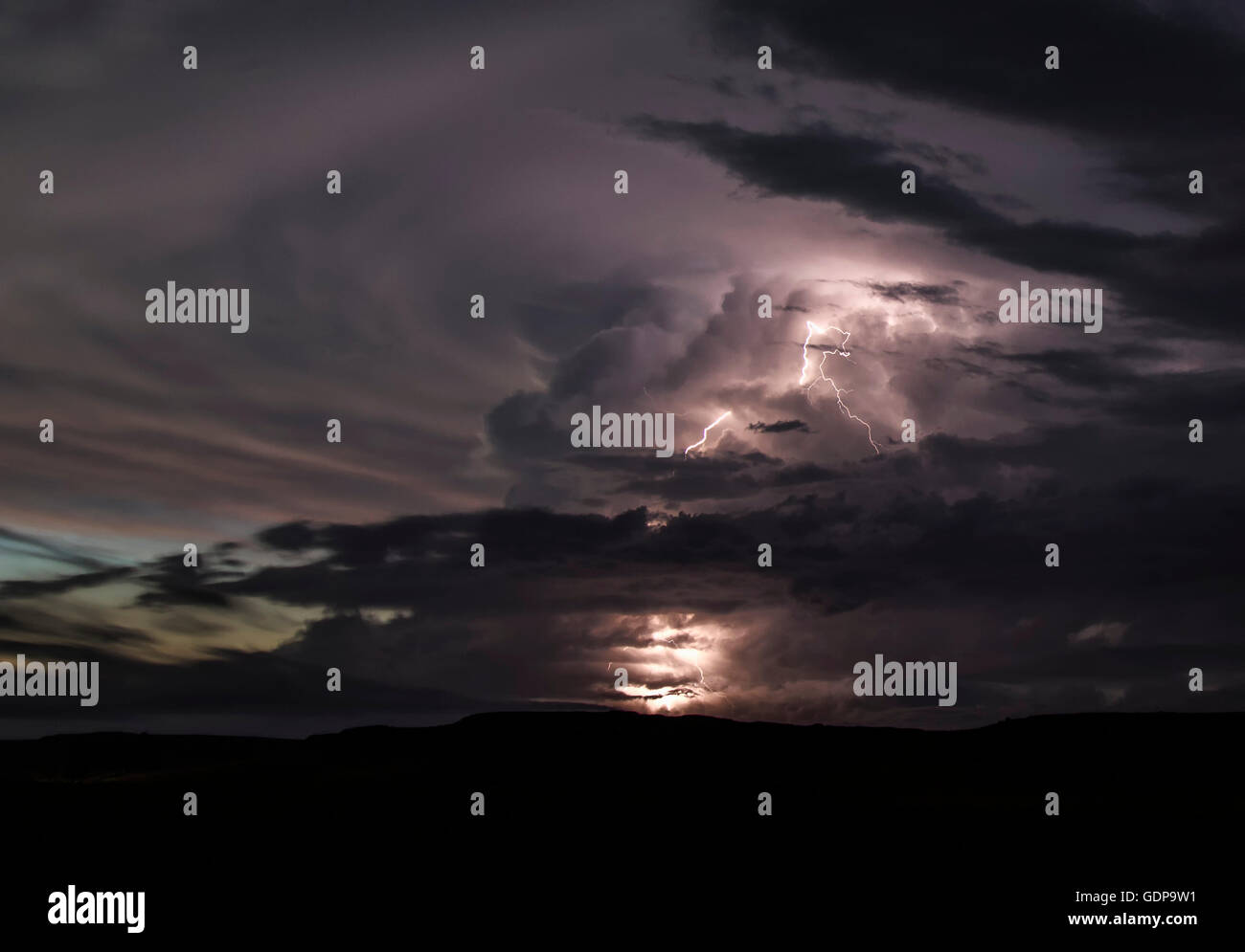 A powerful updraft ricochets off the stratosphere creating a large, expanding anvil cloud.  Lightning shoots out - Stock Image