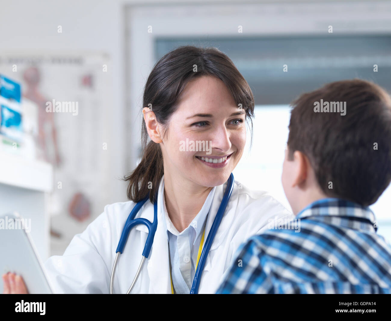 Doctor smiling at boy - Stock Image