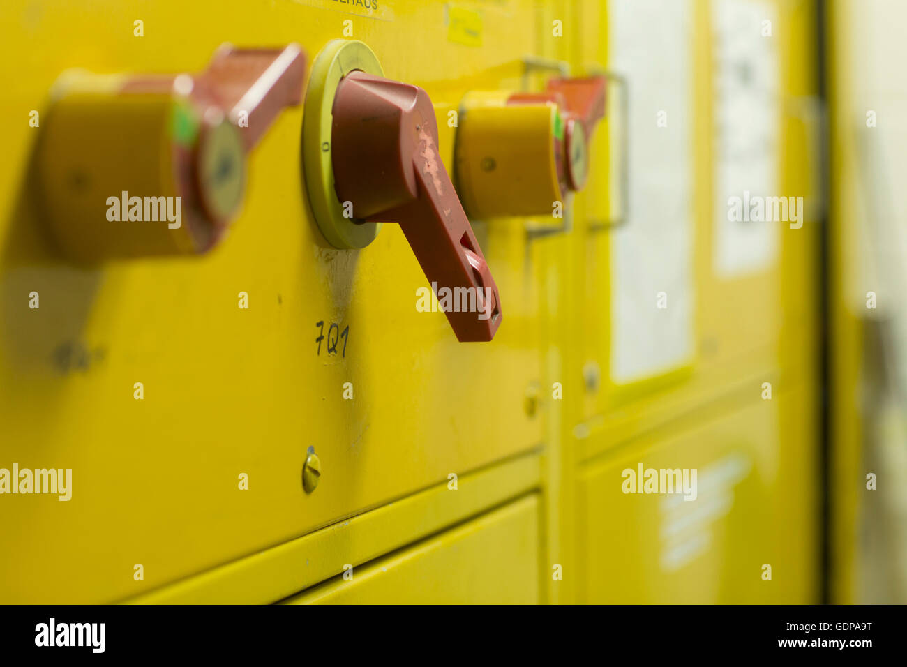 Close up of levers on yellow control panel - Stock Image