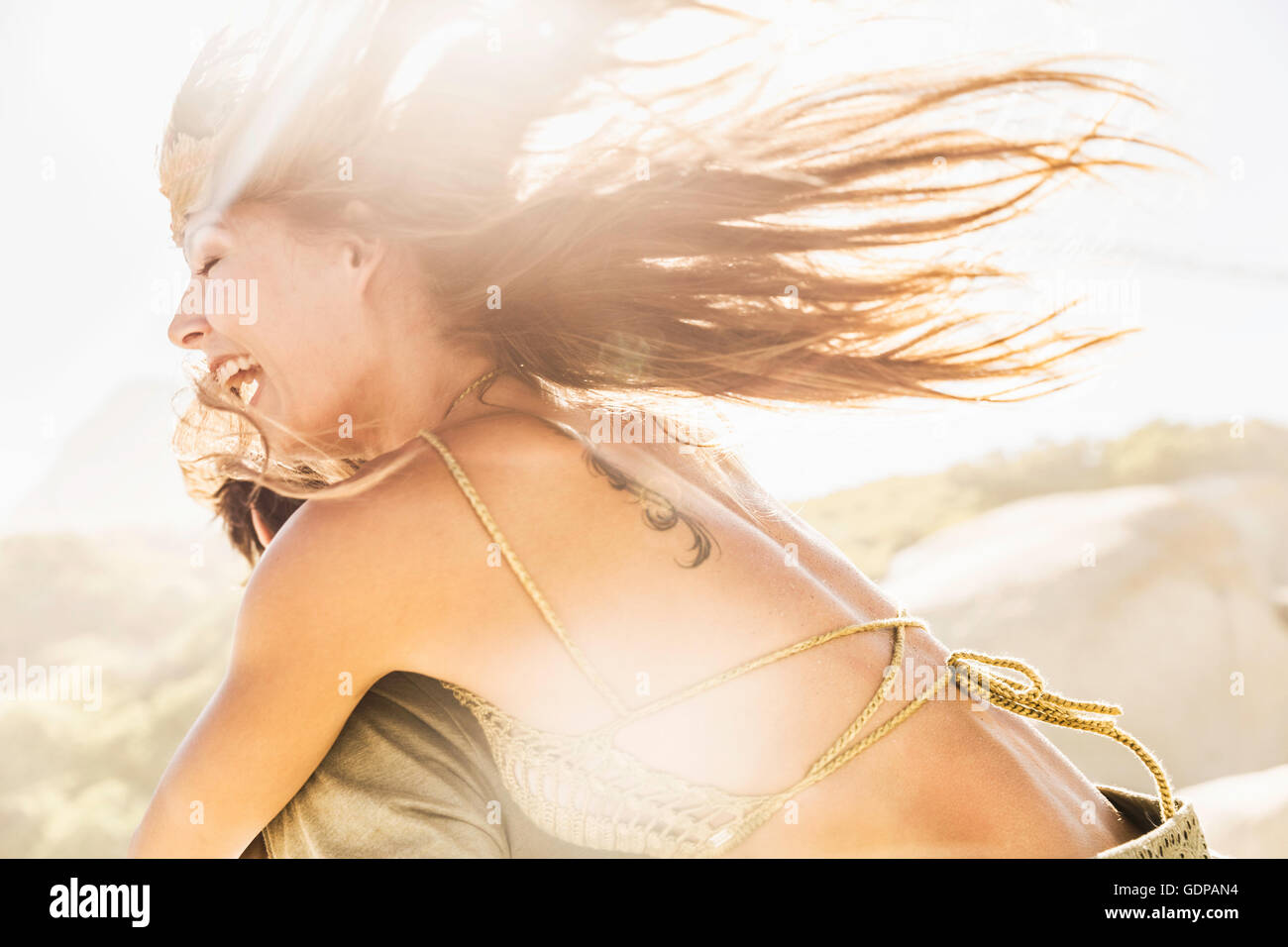 Woman getting running piggy back on sunlit beach, Cape Town, South Africa Stock Photo