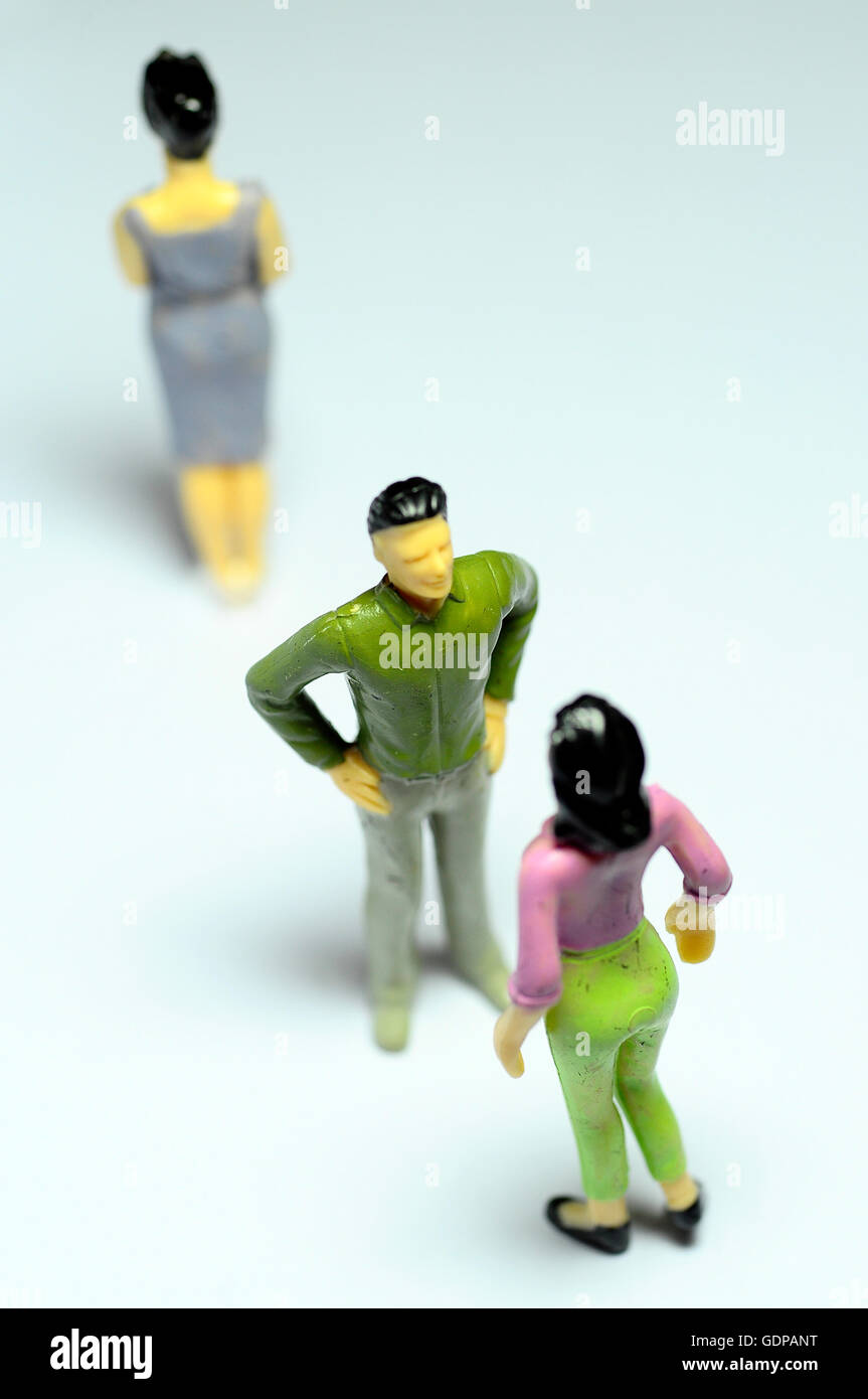 Miniature Man chatting with woman, and single woman turning back - Stock Image