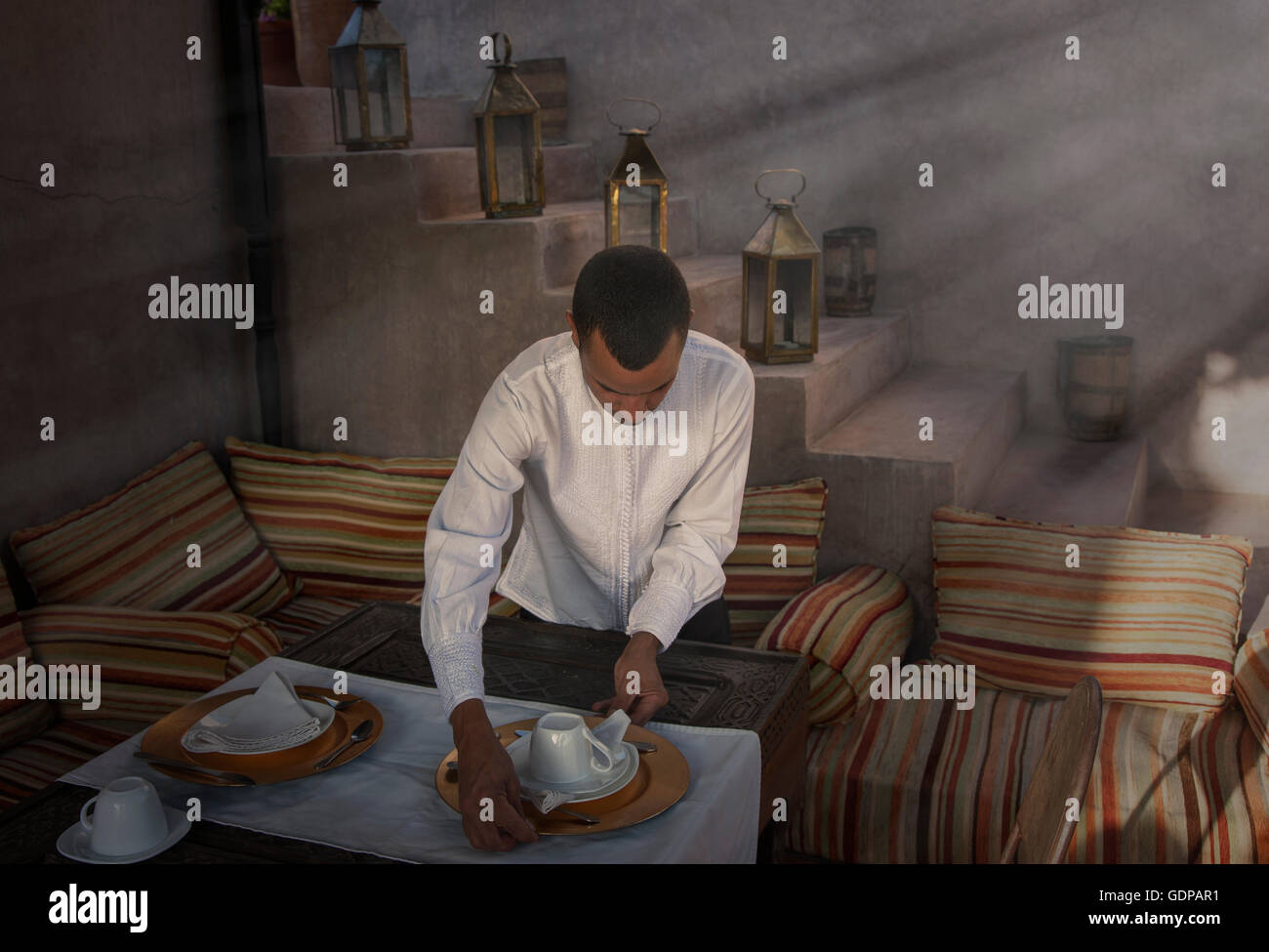 Waiter preparing place settings, Marrakesh, Morocco - Stock Image