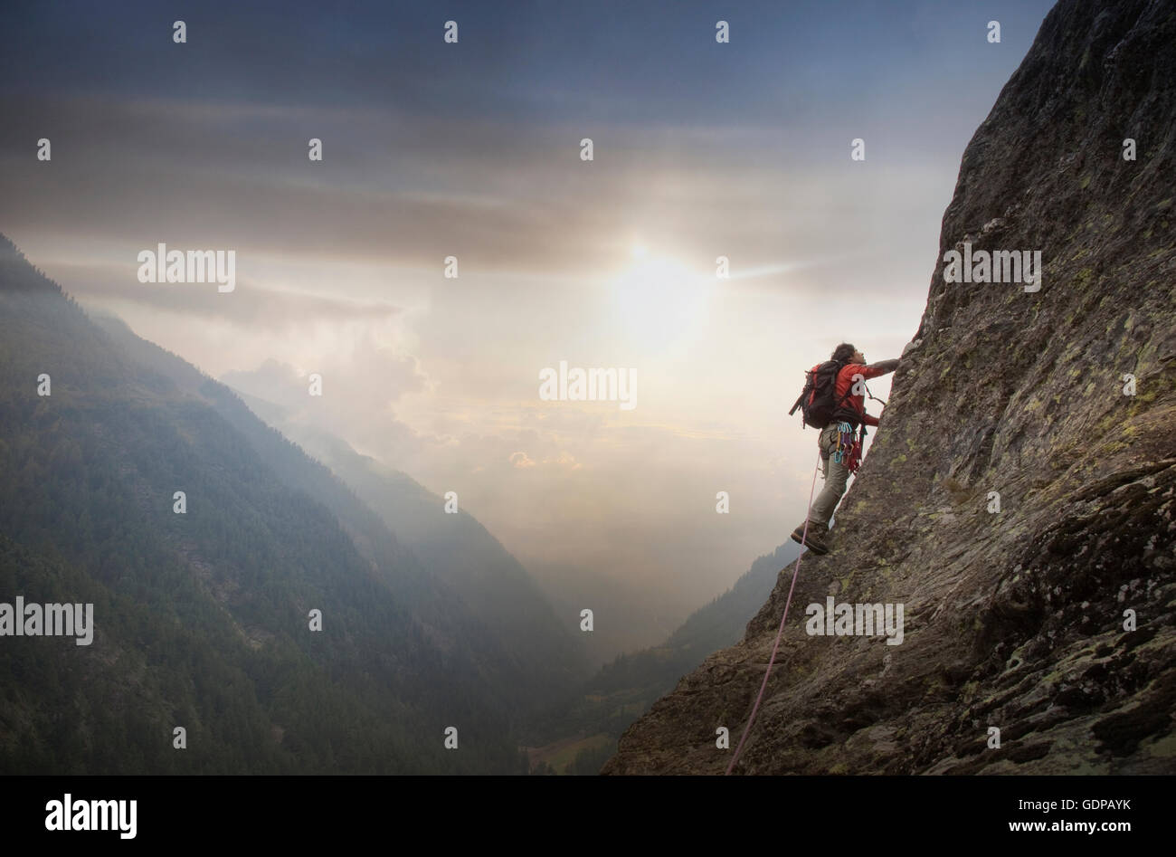 Climber on a rocky wall above a valley, Alps, Canton Bern, Switzerland Stock Photo