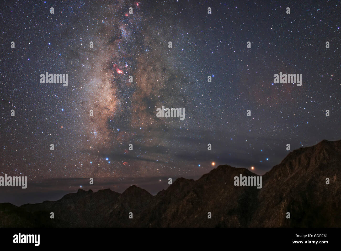 Diffuse starlight and dark nebula along the central bulge of our Milky Way Galaxy set over Mount Balang in Sichuan - Stock Image