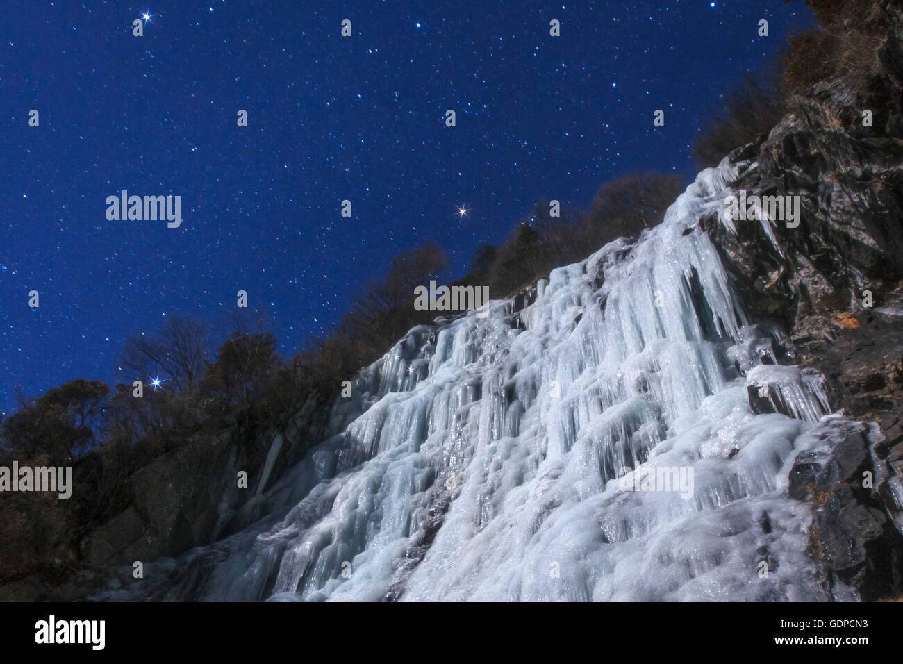 Stars of the Winter Triangle shine above an icefall on a moonlit night in the Sichuan province of China. - Stock Image