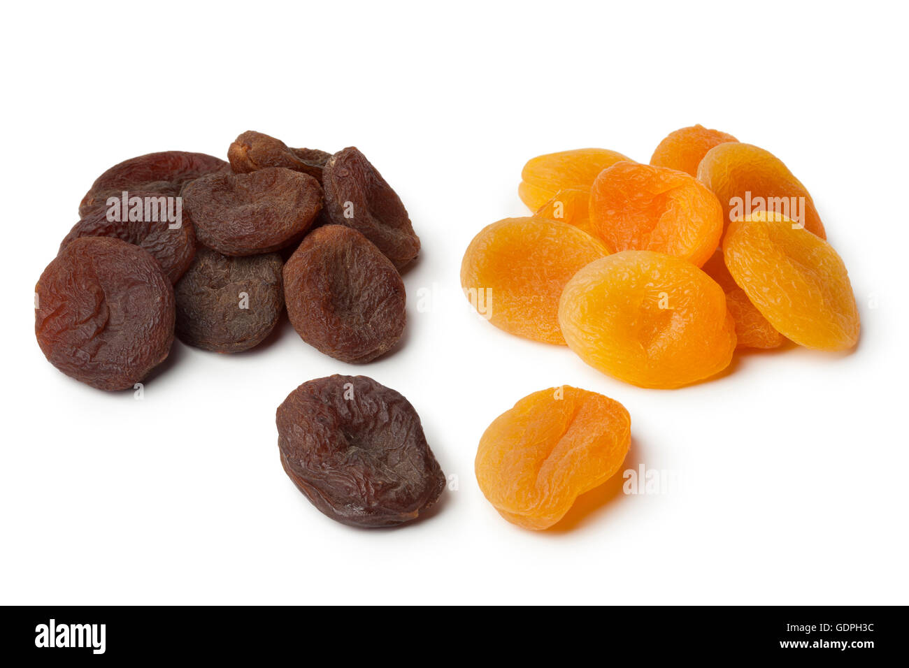 Heap of healthy nutritious brown and orange dried apricot fruit on white background - Stock Image