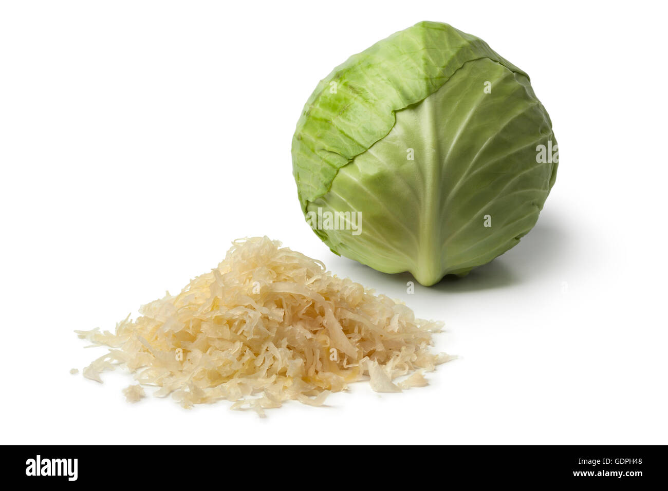 Fresh white cabbage and a heap of preserved sauerkraut on white background - Stock Image