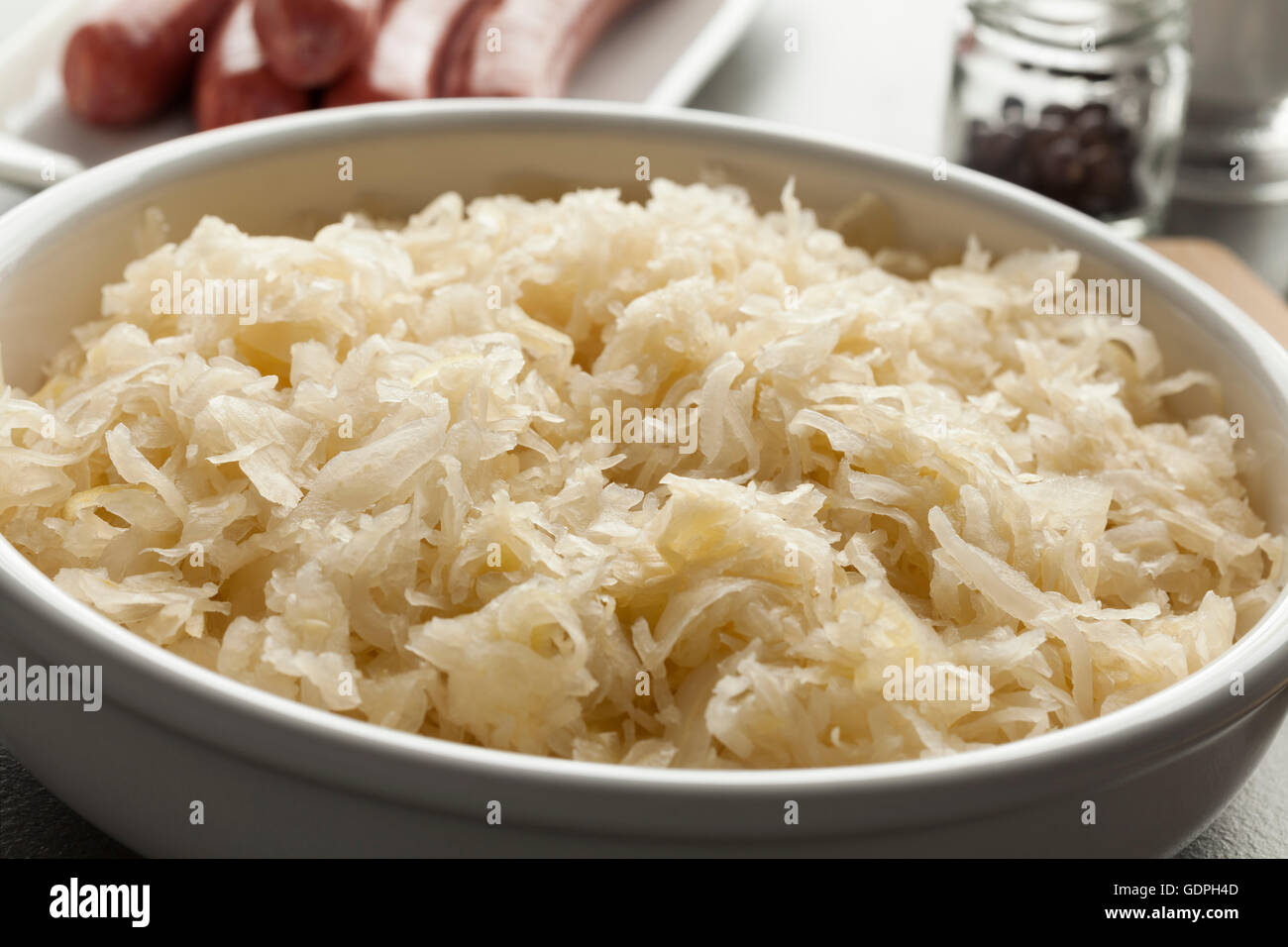 Bowl with raw preserved sauerkraut ready to cook - Stock Image