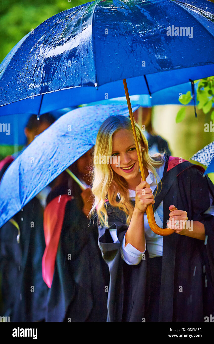 Young woman, walking in the rain, after graduating in at a Cambridge university - Stock Image