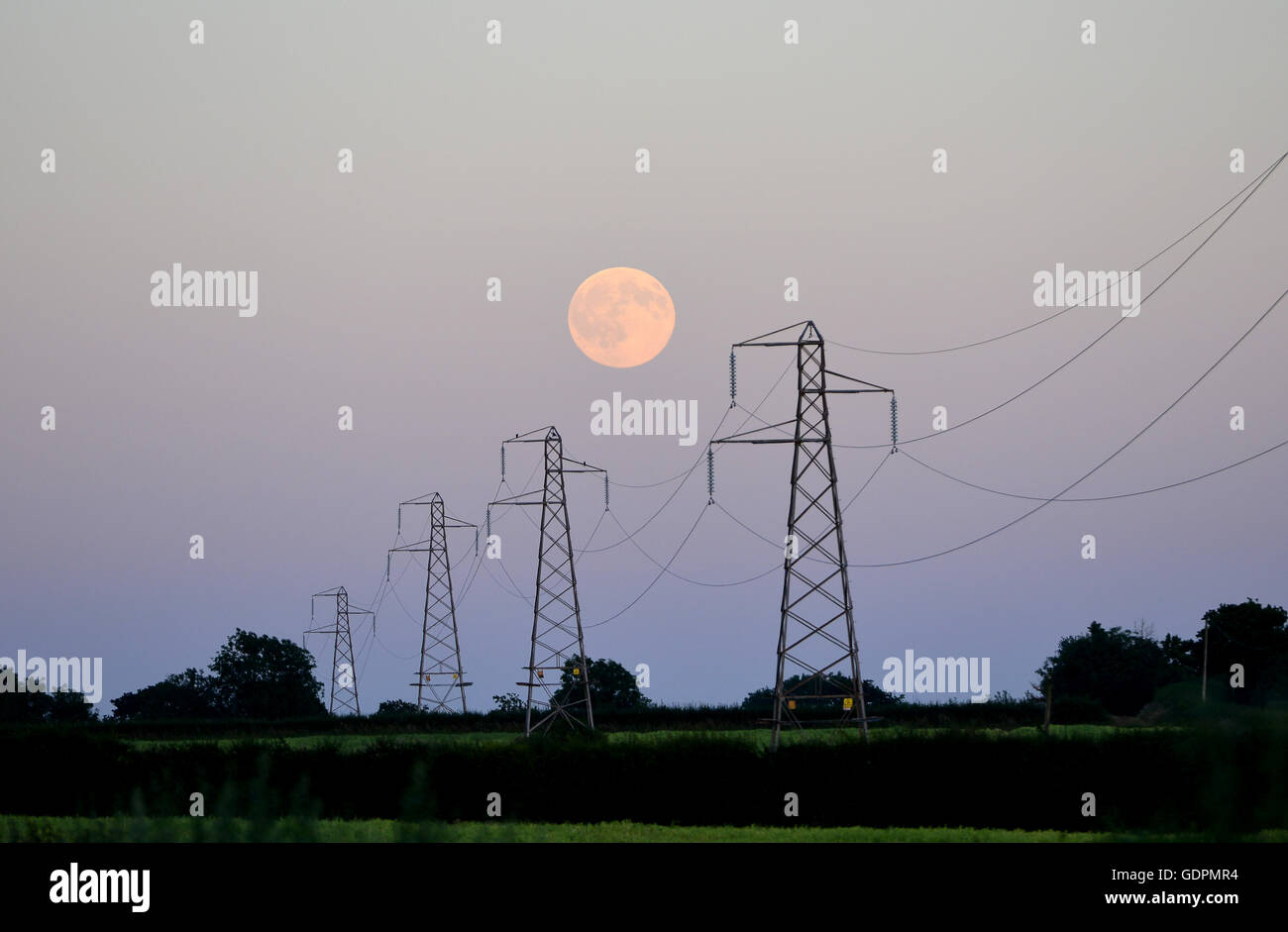 Full moon rising behind electricity pylons - Stock Image