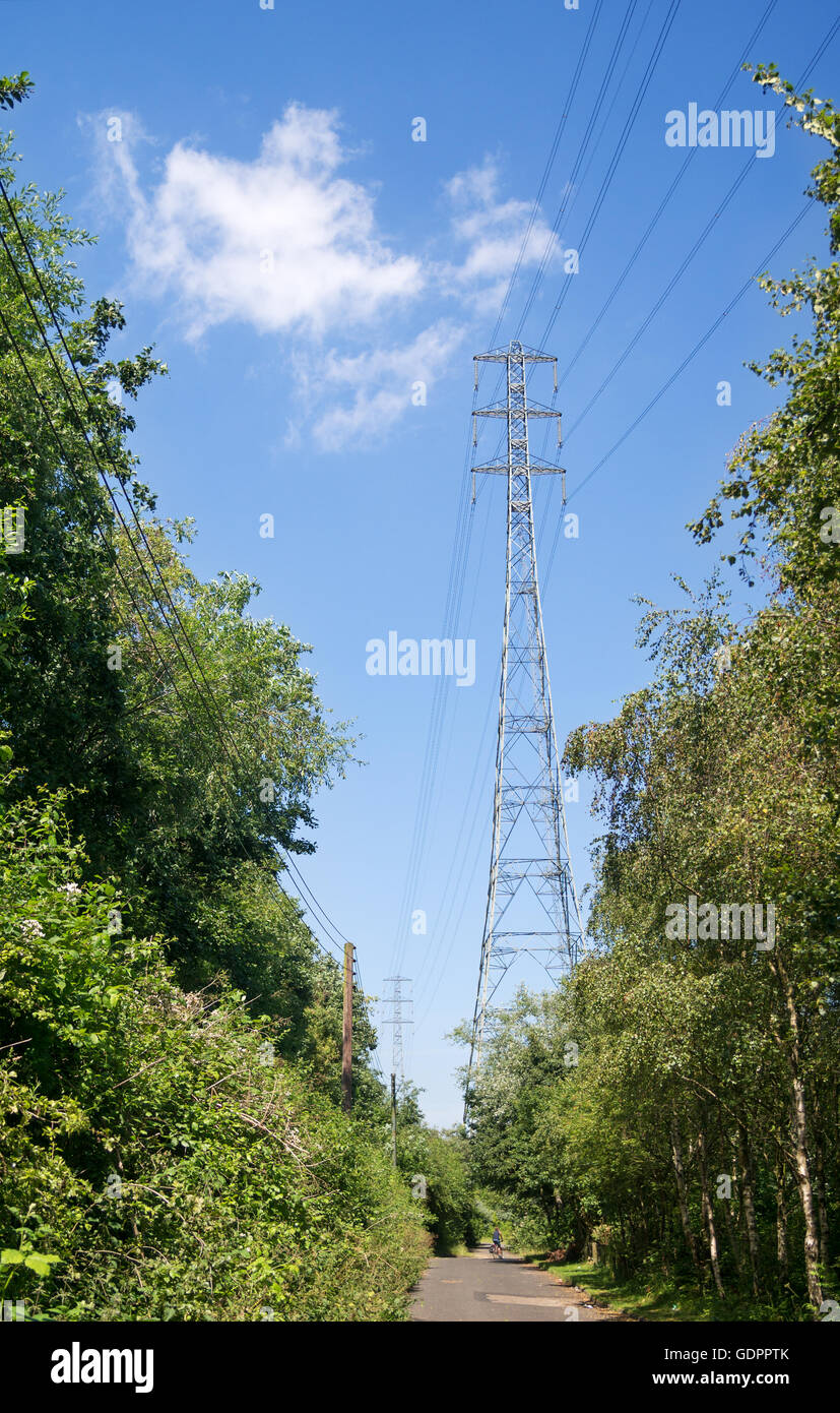 The oversize pylons carrying cables over the river Tyne at Jarrow dwarf a cyclist,  Tyne and Wear, north east England, - Stock Image