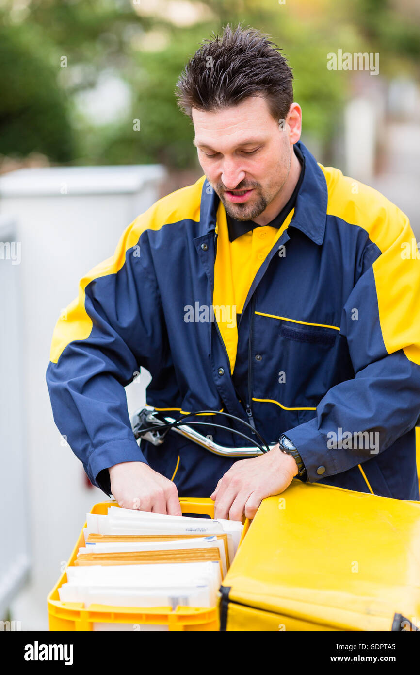 Postman delivering letters to mailbox of recipient - Stock Image