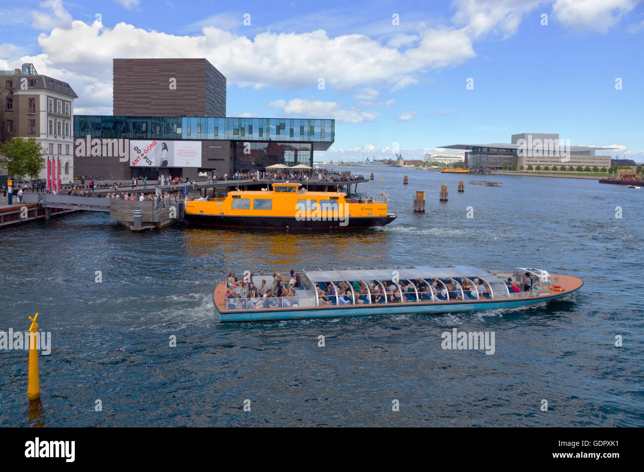 A canal cruise boat and a yellow harbour bus at the Royal Playhouse in Copenhagen. The Royal Opera House opposite - Stock Image